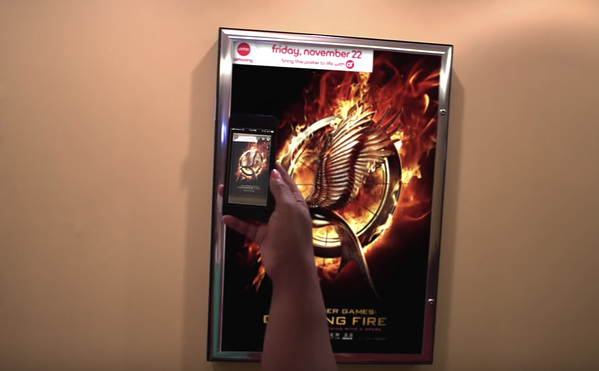 a person scans a hunger games movie poster for more information with the AMC theater app